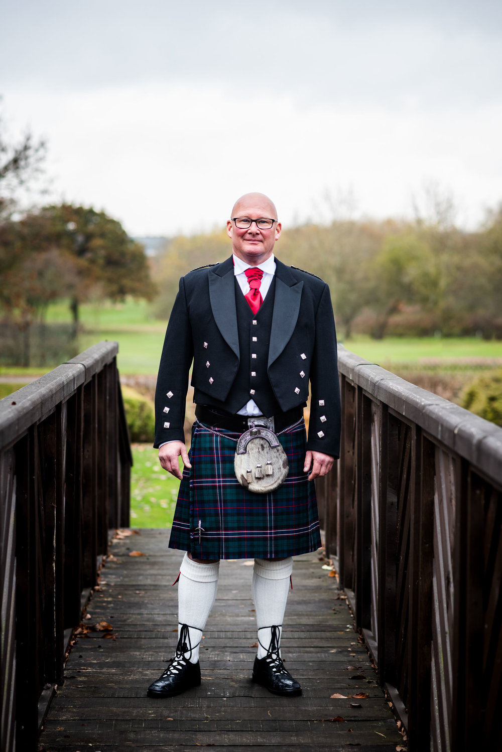 Groom Duncan in his kilt stood on the feature bridge of The Abbey Hotel Redditch