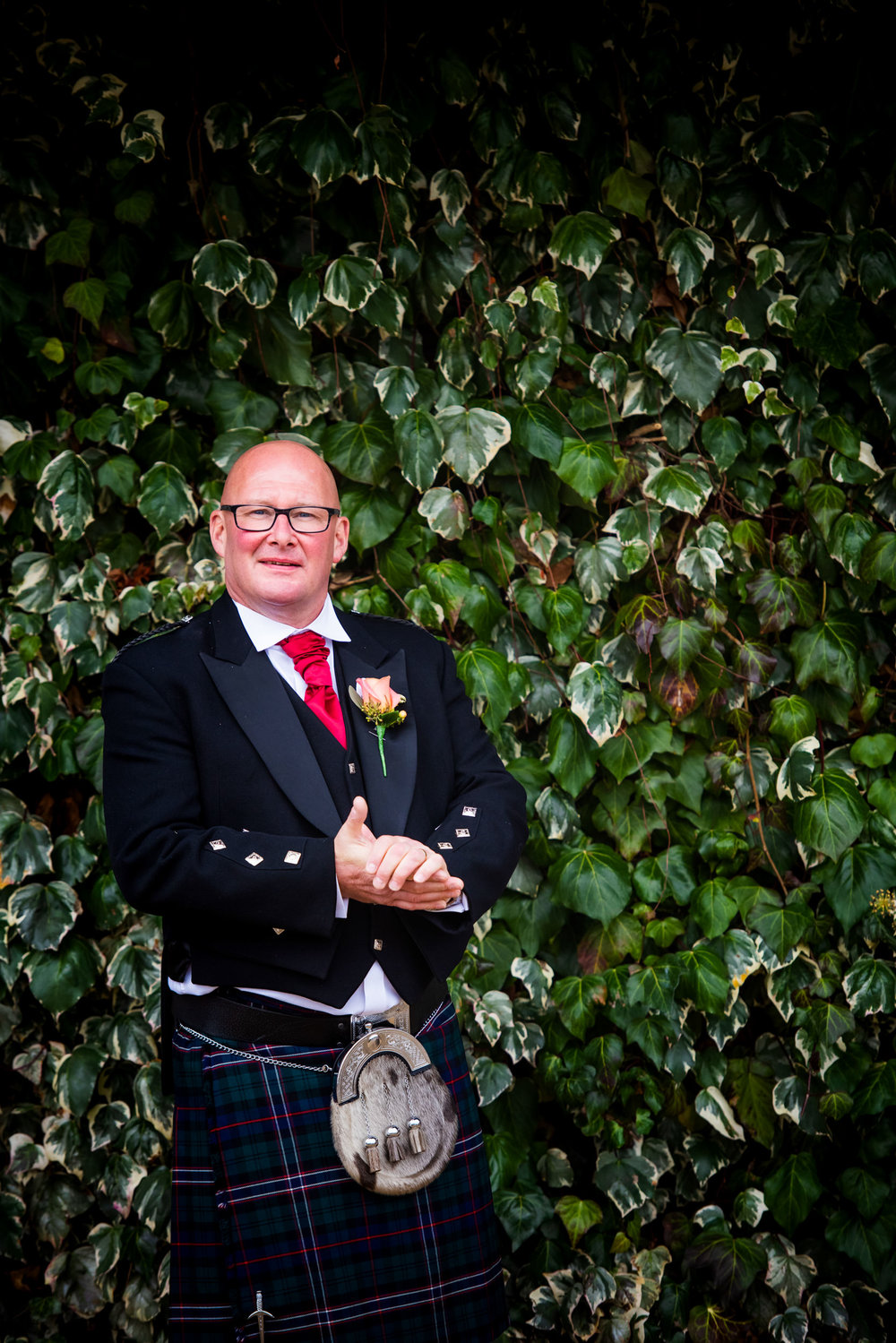 Groom stood in front of an Ivy wall
