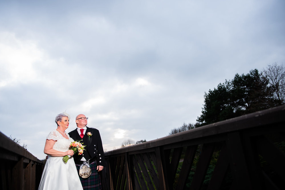 Bride and Groom stood on the feature bridge on the golf course at the Abbey Hotel