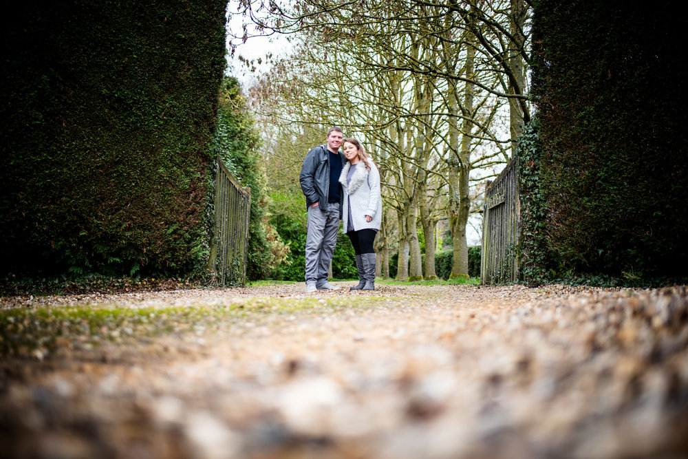 Engaged couple stood in wooded gateway at Arrow Valley Lake, Worcestershire