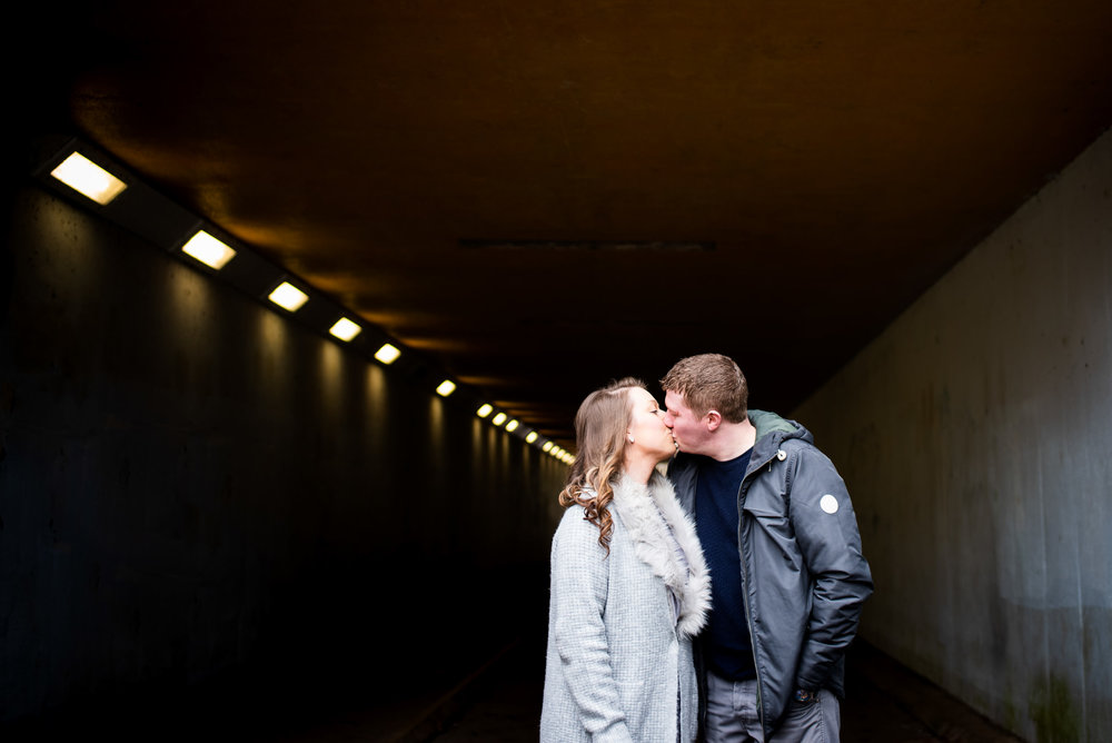 Couple kissing in the soft light of an underpass