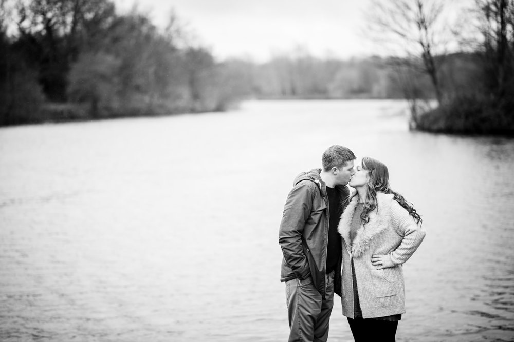 Engaged couple kissing at the edge of Arrow Valley Lake