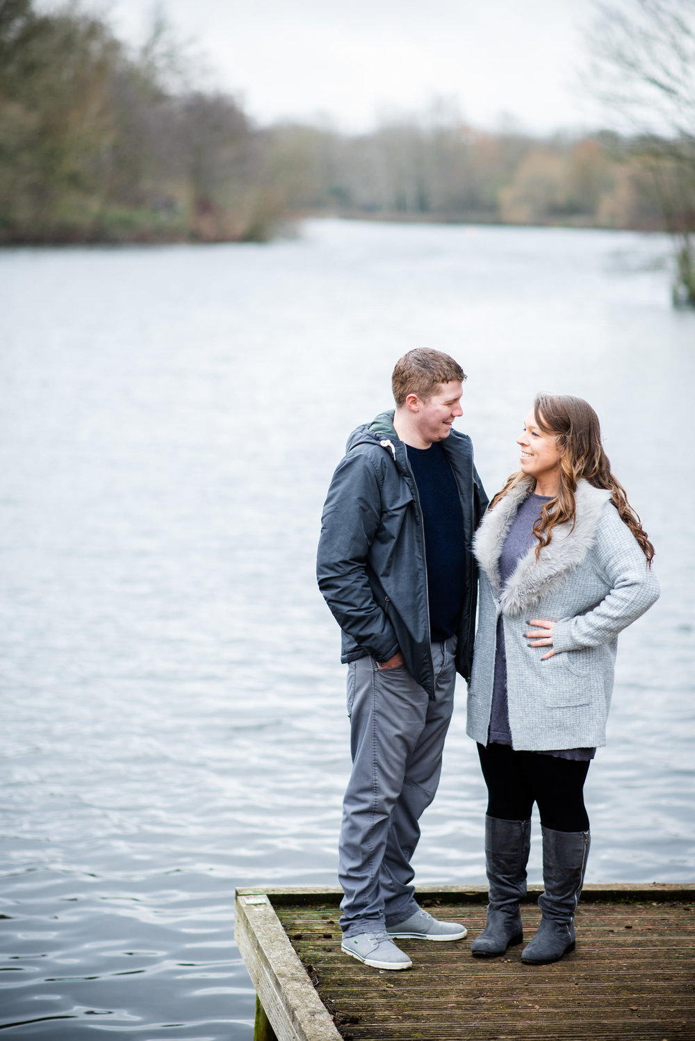 Couple stood on the edge of a blue lake looking at each other lovingly