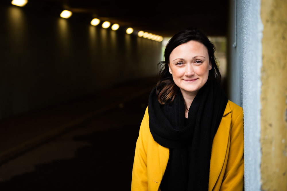 Woman in a yellow coat stood in the soft light of an underpass