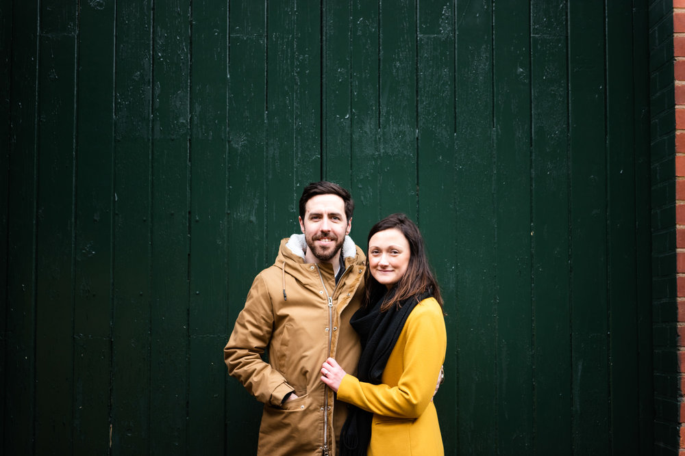 Smiling happy couple stood in front of dark green gate at Arrow Valley Lake, Worcestershire