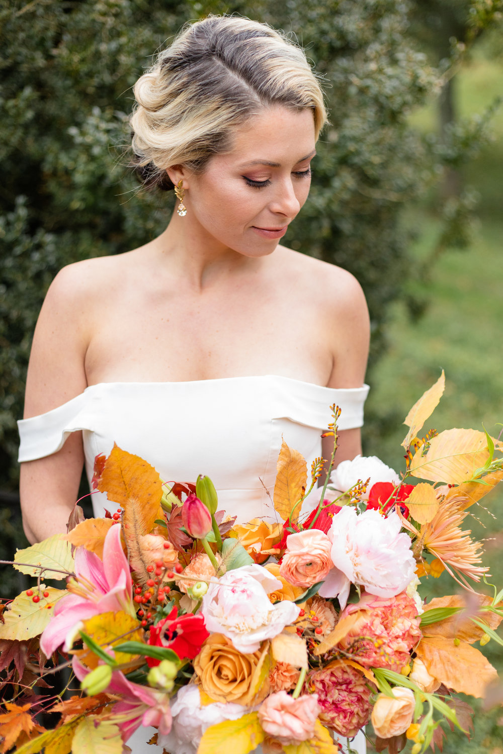 sleek, modern bride looking at full bouquet. Autumn wedding, Catesby Farm Estates, classic, classy wedding.