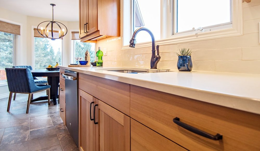 Wood cabinets with Caesarstone Buttermilk quartz counters and subway tile backsplash. Blue leather dining chairs