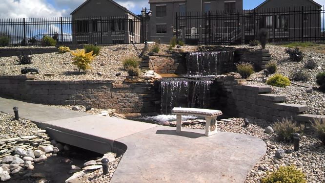 Outdoor-living-waterfall-stamped-concrete-landscaping.png