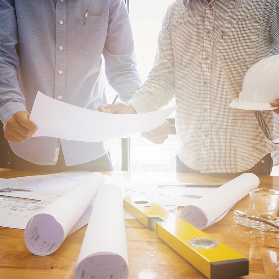 Two people examining blueprints
