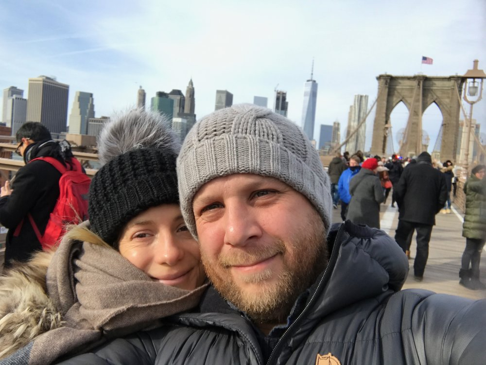 Jason and Leslie walking across the Brooklyn Bridge on a chilly day to find the best dumplings in Chinatown