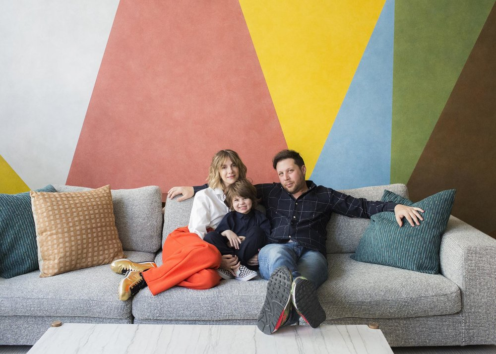 Sitting on our sofa in front of our colorful wall mural