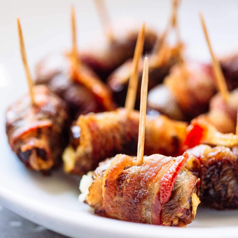Bacon Wrapped Dates Stuffed with Blue Cheese - It doesn't get much simpler or savoury than this bacon-filled recipe! Stuff dates with goat cheese, generously wrap in bacon and bake. Serve warm and crispy! We know this one will become a family favourite!Get the recipe>>