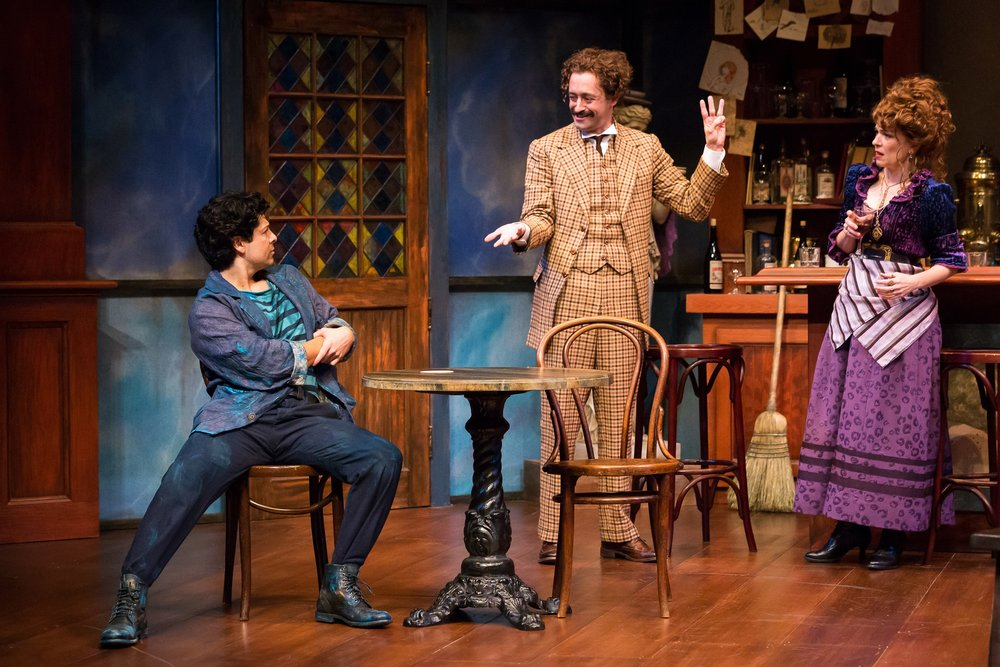 Joseph Castillo-Midyett as Pablo Picasso, Dylan Godwin as Albert Einstein, and Elizabeth Bunch as Germaine in the Alley Theatre's production of  Picasso at the Lapin Agile  by Steve Martin. Directed by Sanford Robbins. Photo by Lynn Lane.