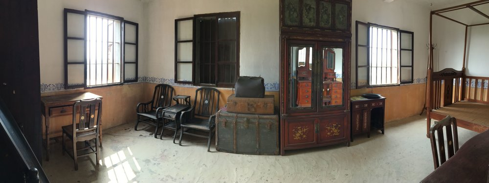Panorama view of a long, narrow bedroom