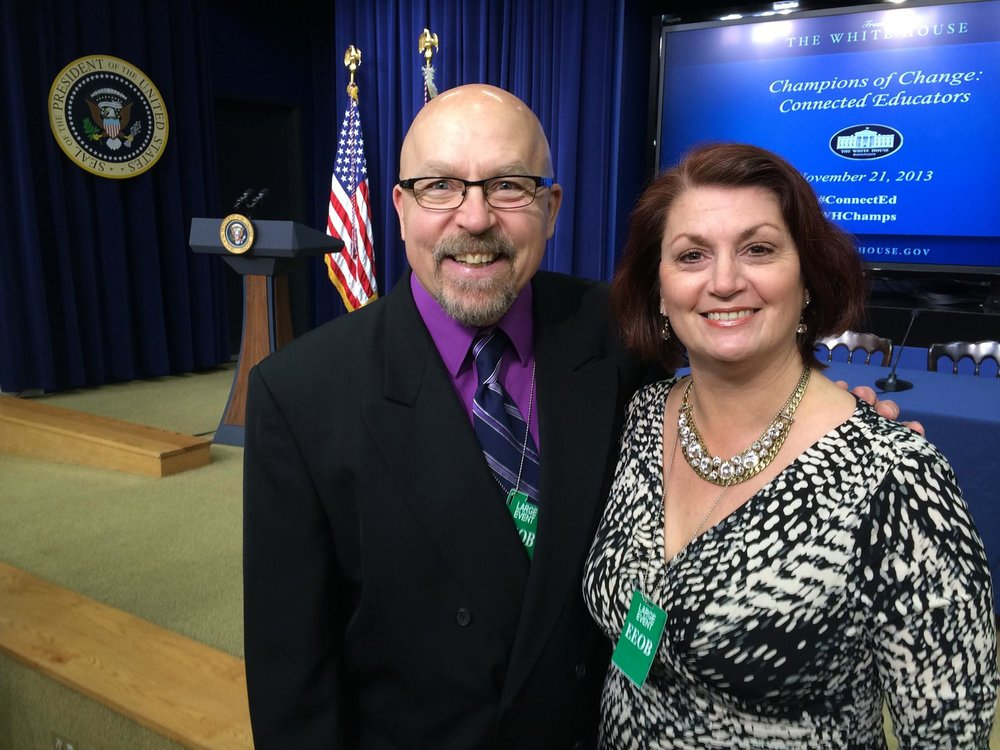 Mark and Rachel Coppin posing in the White House in front of a Champion of Change banner.
