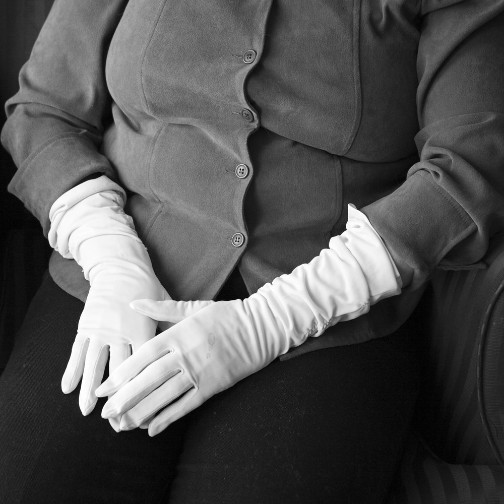 Wearing her mother's gloves.