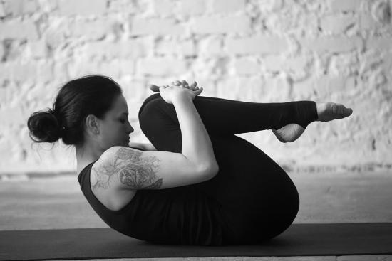 back-flexion-stretch-as-woman-on-yoga-mat-hugs-her-knees-to-her-chest.jpg