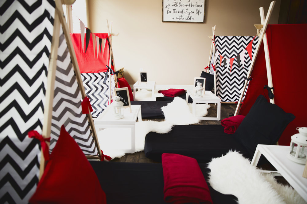 Modern Man Cave - The feel of this theme is certainly masculine, but without compromising style and comfort! The modern man-cave is decorated with black and white chevron and bold red with plush carpets that provide texture and of course, a soft spot to sit! Flag banners are hung festively.