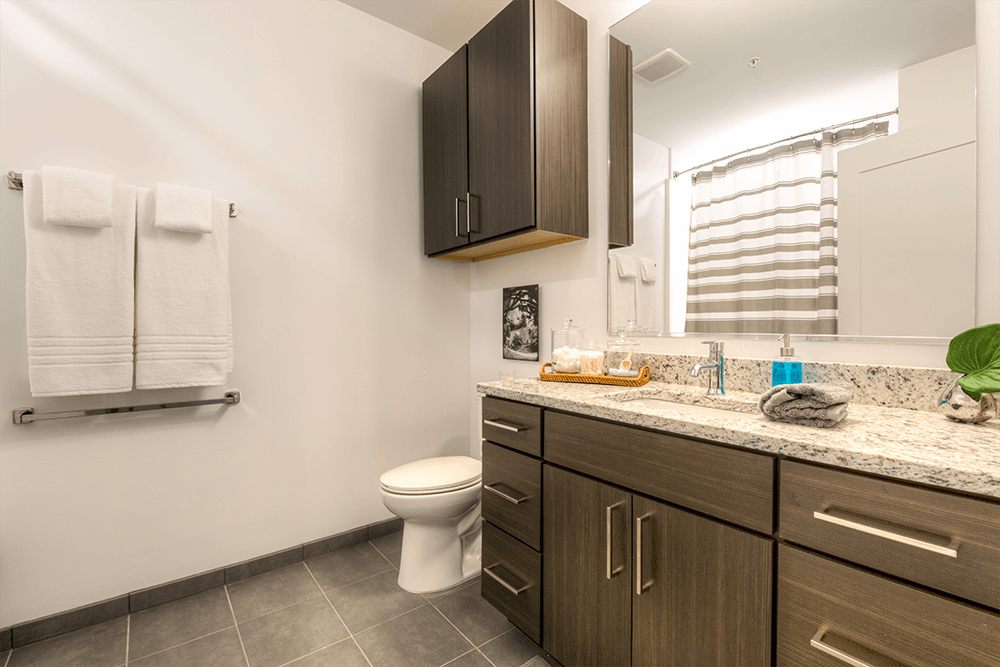 Ceramic tile bathrooms feature plenty of storage in gorgeous espresso wood-look laminate cabinets with white/black granite countertops and nickel pulls