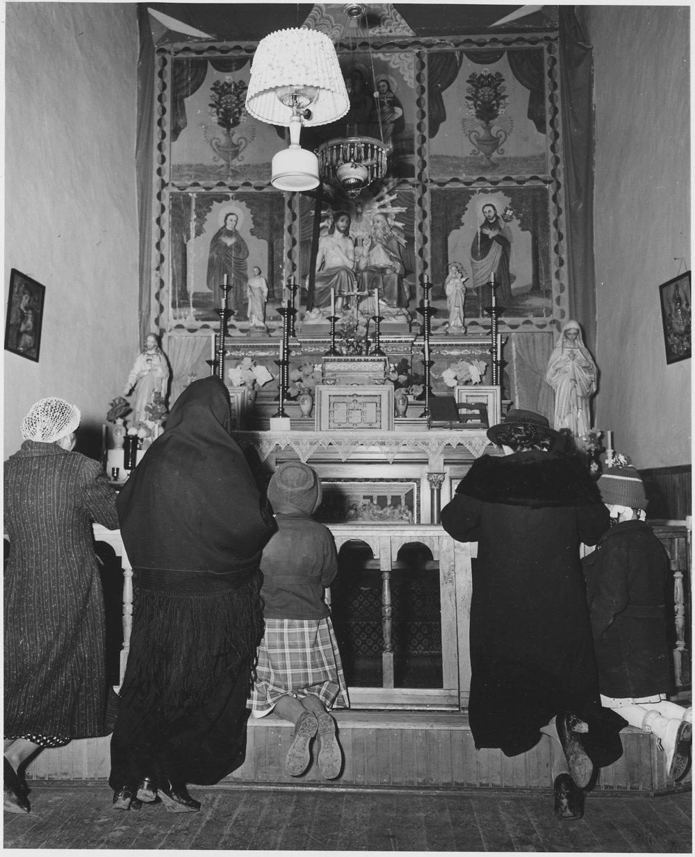 Taos_County,_New_Mexico._Prayer_before_altar_of_church_at_Arroyo_Seco._-_NARA_-_521929.jpg