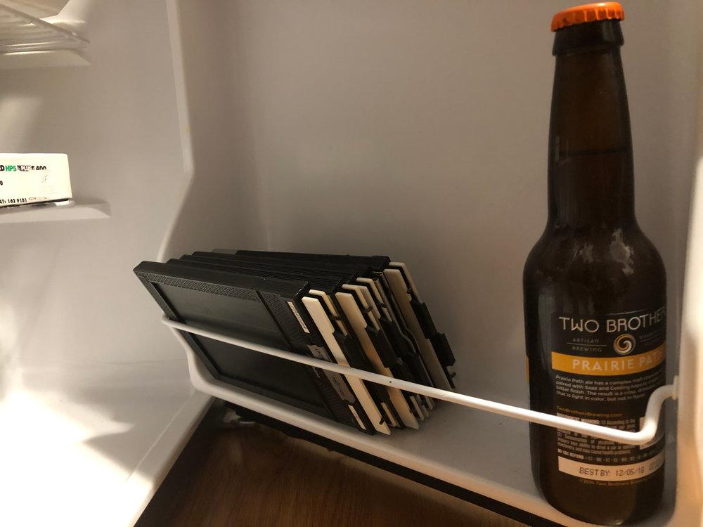 Five film holders next to my last beer in my fridge