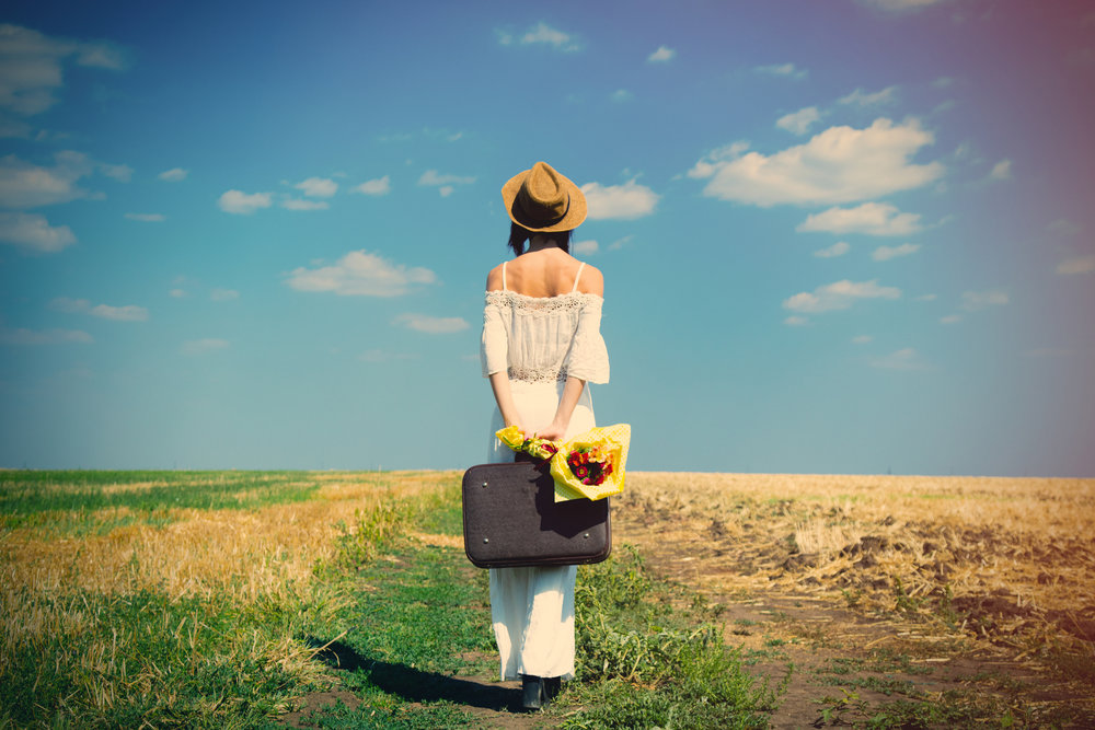 girl in field with suitcase.jpg