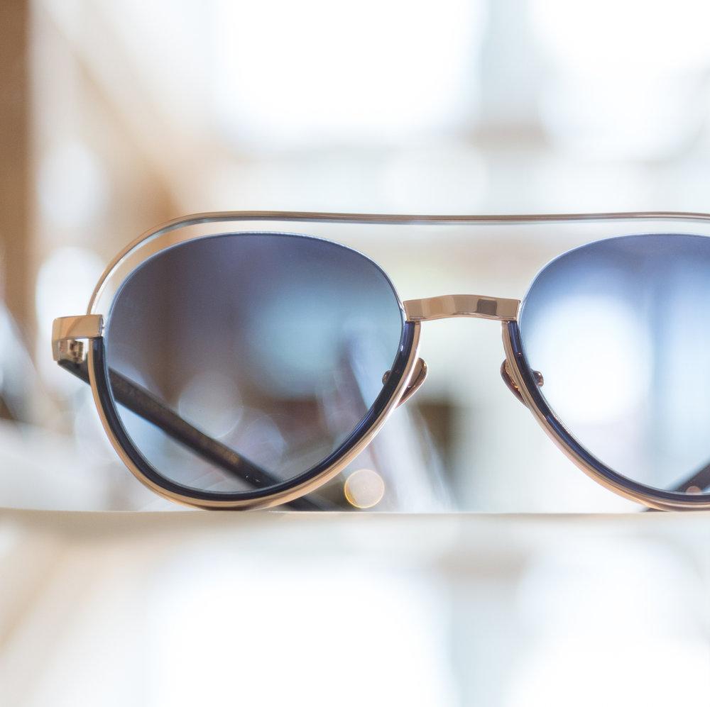 sunglasses on a shelf in a window