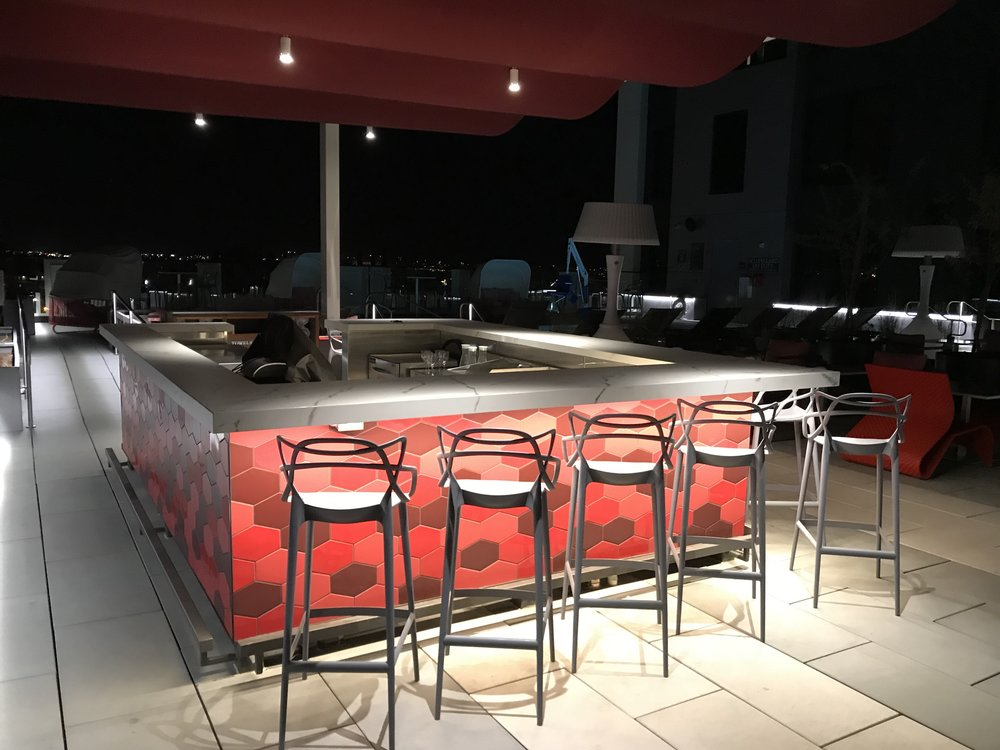 Rooftop bar and patio area adjacent to the pool