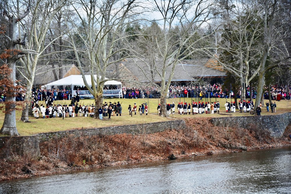 Spectators gather on the banks of the Delaware river to view the reenactment.
