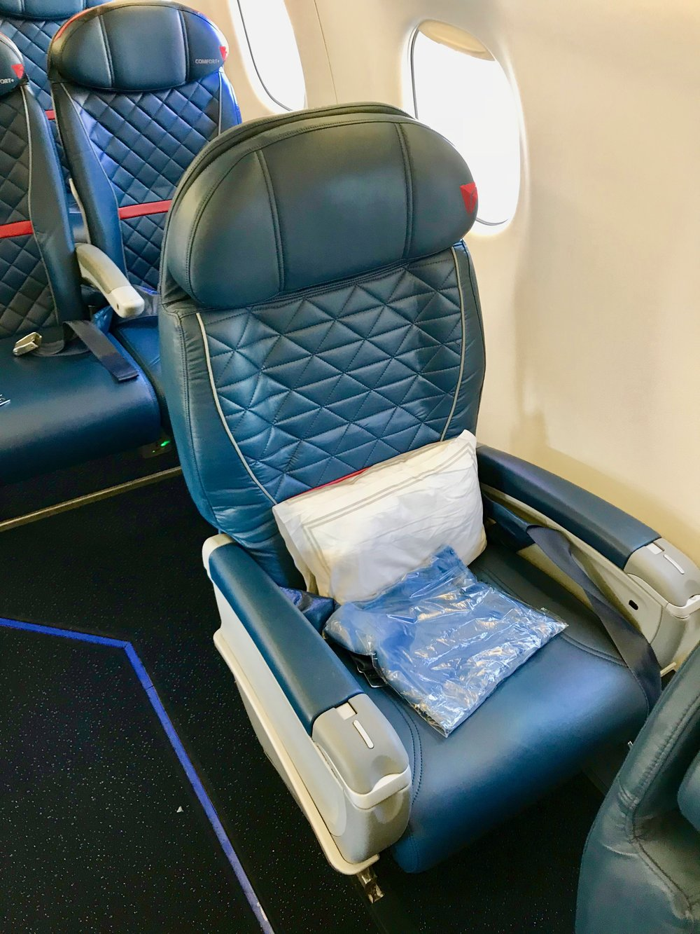 Seat 5A is directly behind the last single-seat in First Class (pictured). Seat 5A has additional legroom and easier aisle access due to the position of seat 4A. There is a power outlet under the seat.