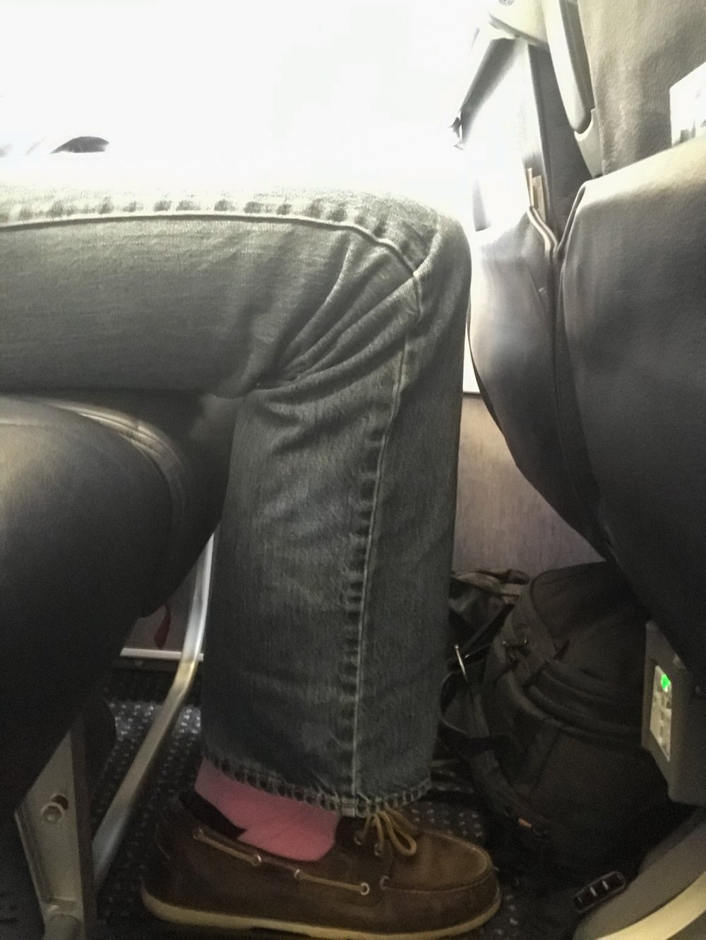 I'm 72 inches tall and had an extra inch or two to spare before my knees touched the seat in front of me. My seatmate was a little taller than me and complained about the legroom.