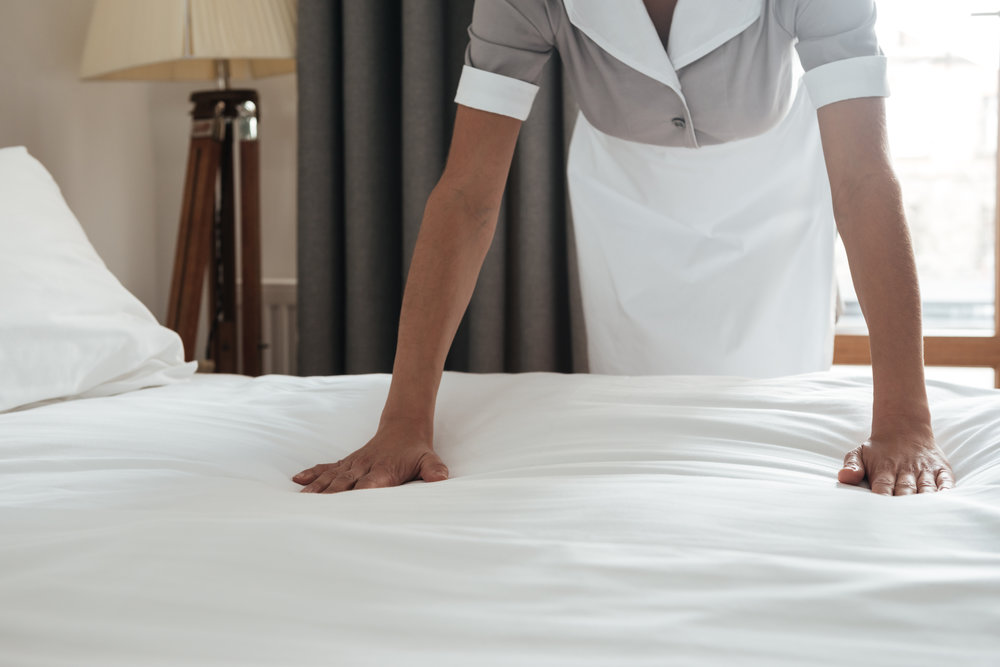 cropped-image-of-a-chambermaid-making-bed-in-PQLKX82 (1).jpg