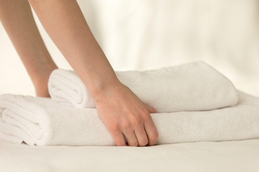 maid-placing-stack-of-towels-on-the-bed-P5YT3RQ.jpg