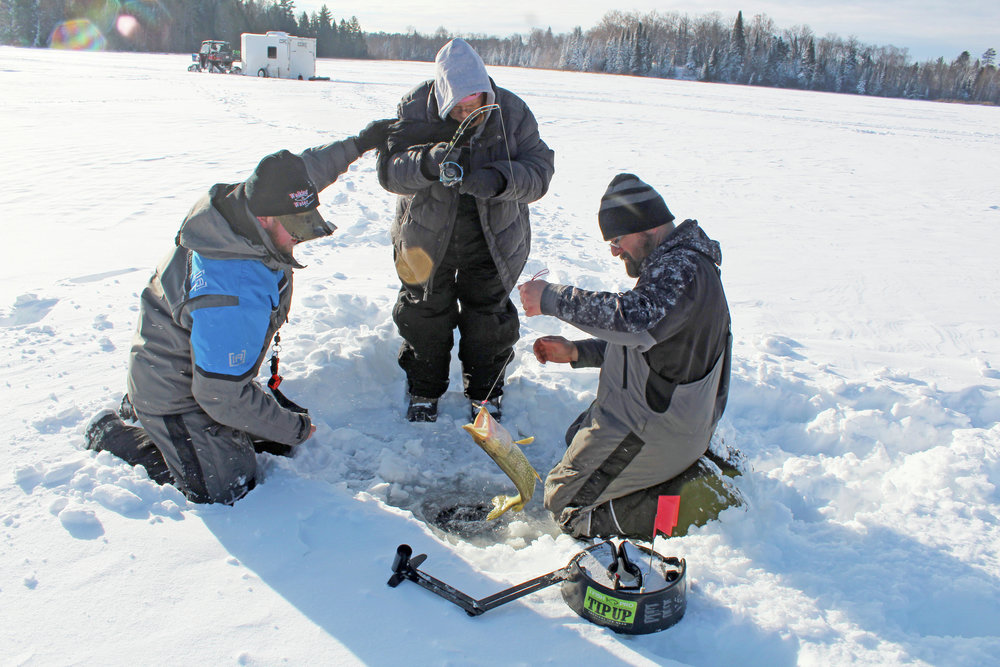 With the help of Walking on Water Outdoors (WOW) on Saturday, Darla Olson caught her bucket-list fish: a northern pike. Assisting her were Brenden Mattson, at left, and WOW founder Tim Schmid. (Photos by Shannon Geisen/Enterprise)