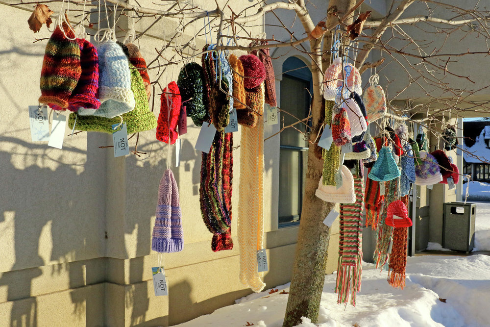"""Knitted hats and scarves hang from trees in front of the Brainerd Police Department Friday, Jan. 4, and are there for those who need them. Tags attached to garments proclaim """"I am not lost! If you are cold, please take me to keep you warm."""" On its Facebook page, Utrinkets reported the new items were placed on the Giving Trees with an agreement with the police department. Kelly Humphrey / Brainerd Dispatch"""