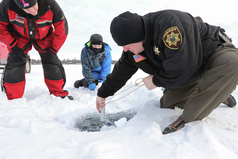 Crow Wing County Sheriff Scott Goddard measures the ice Thursday, Jan. 17, as Clint Meyer with the Brainerd Jaycees and his son Quinnten Meyer watch. The ice check was to make sure there would be enough ice for the annual Brainerd Jaycees $150,000 Ice Fishing Extravaganza on Hole-in-the-Day Bay on Gull Lake. The contest is scheduled Jan. 26. Kelly Humphrey / Brainerd Dispatch