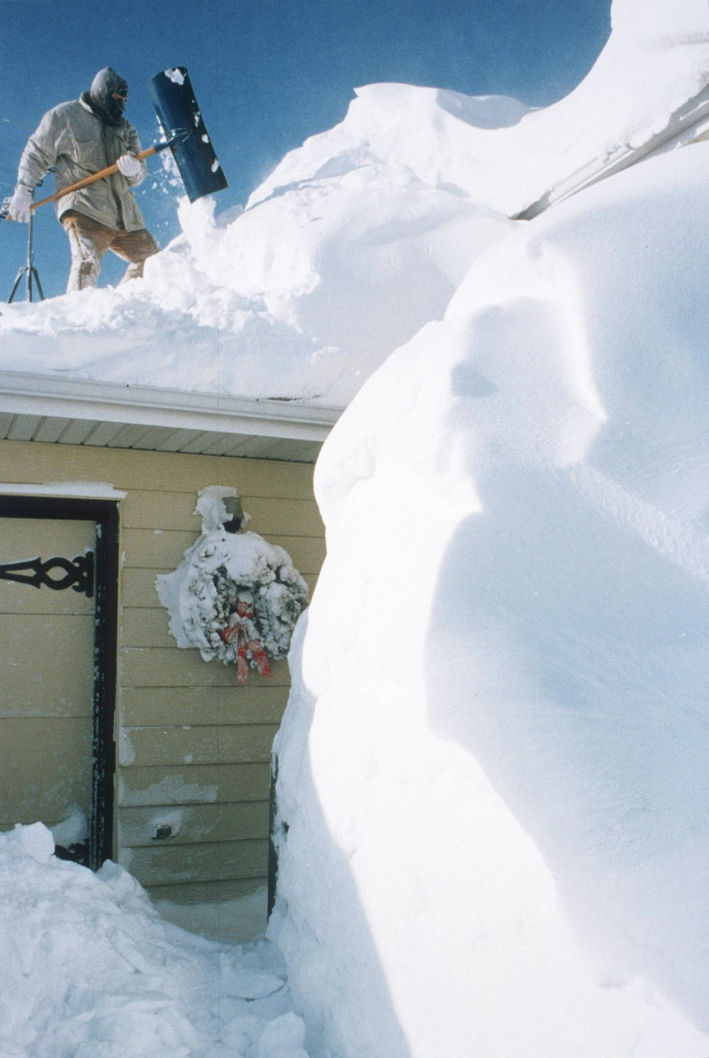 Jerry Walker shovels a mountain of snow from the top of his Dilworth home so the roof won't collapse under the weight. Forum News Service file photo