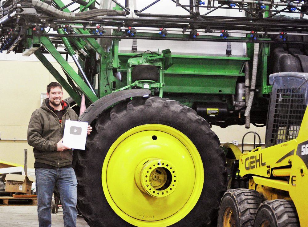 Zach Johnson poses with his 100,000 subscriber plaque in front of his farming equipment. (Jared Rubado / Echo Press)