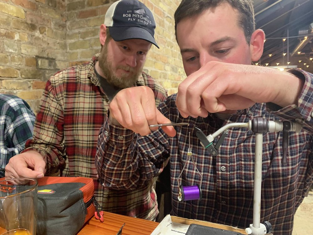 Mark Houle, right, ties a small bead-head nymph while Evan Griggs offers a few tying tips. Steve Hoffman / Forum News Service