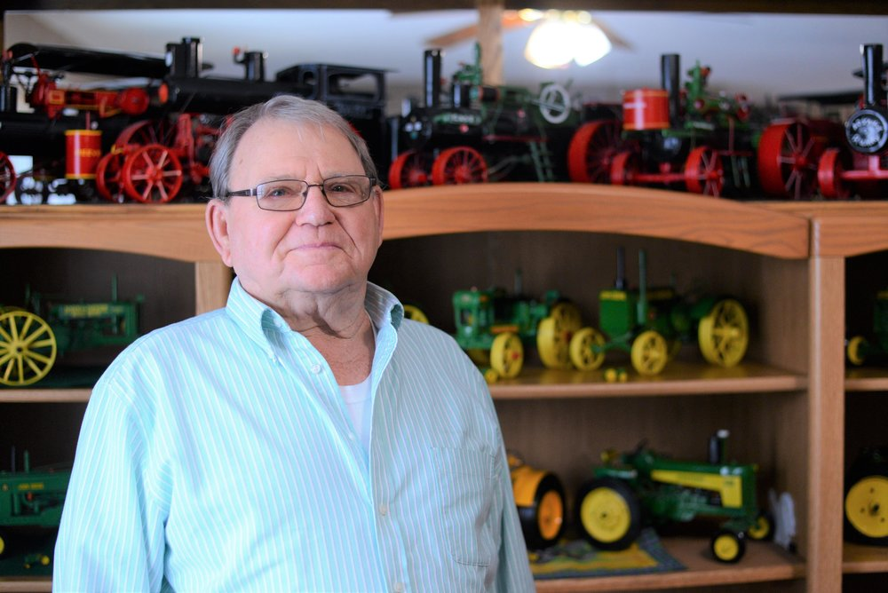"Rod Swanson, 78, poses for a portrait in his home in front of his collection of homemade tractors. ""He worked construction his whole life, we never saw talent like that before,"" his daughter Jodi Sjolie said. (Carter Jones / FOCUS)"