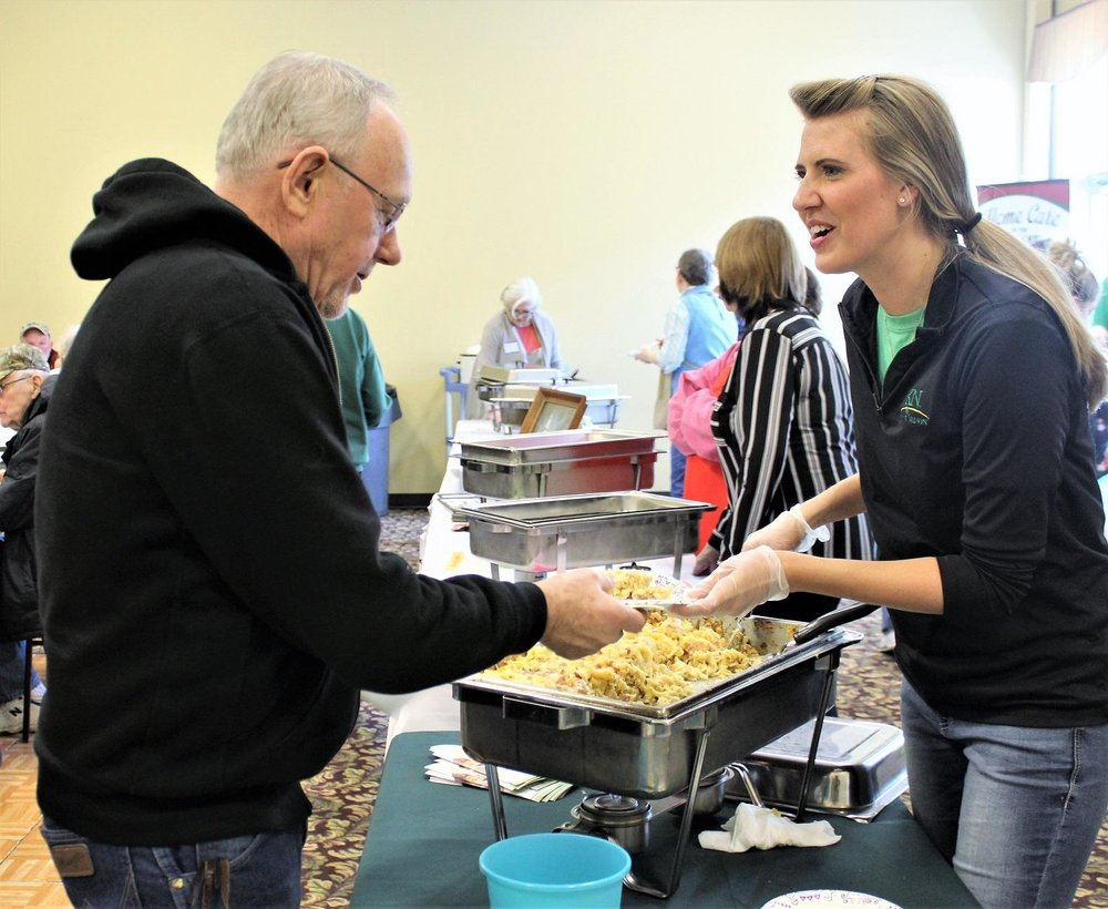 Laura Kremer from Knute Nelson serves up the winning chicken bacon ranch hotdish to Chuck Jensen of Alexandria. (Celeste Edenloff / Echo Press)