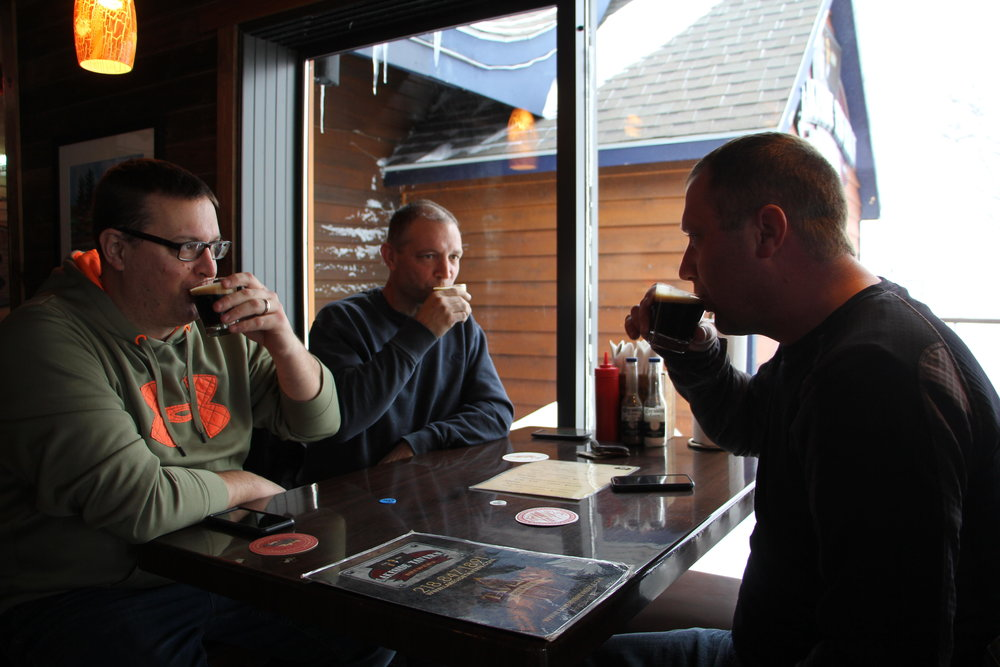 Jason Brands (left), Doug Brands (center), and Travis Vansanten (right) are in town for an ice fishing trip and stumbled out of the cold and into Lakeside for a bite to eat. Lucky for them, they got to enjoy a little free winter shandy as well. Kaysey Price / Tribune