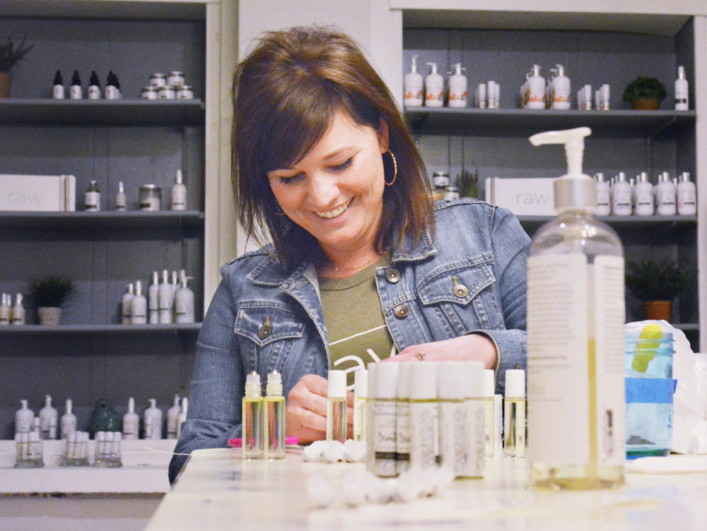 Lindsay Muzik adds labels to aromatherapy jars at RAW.&Co., one of the Alexandria area's newest manufacturers. (Karen Tolkkinen / Echo Press)