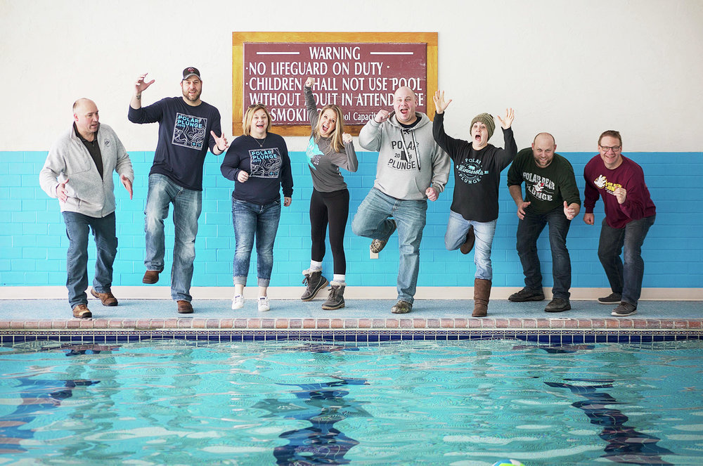 Organizers and Polar Plunge supporters, each wearing shirts from different year's events, pretend to jump in the pool at Arrowwood Resort Sunday. Pictured are (left to right) Keith Melrose, Randy Jansen, Darcie Zirbes , Beth Melrose, Ryan Cook, Jackie Skoglund, Chris Zirbes and Kevin Guenther. (Jennifer Guenther Photography)