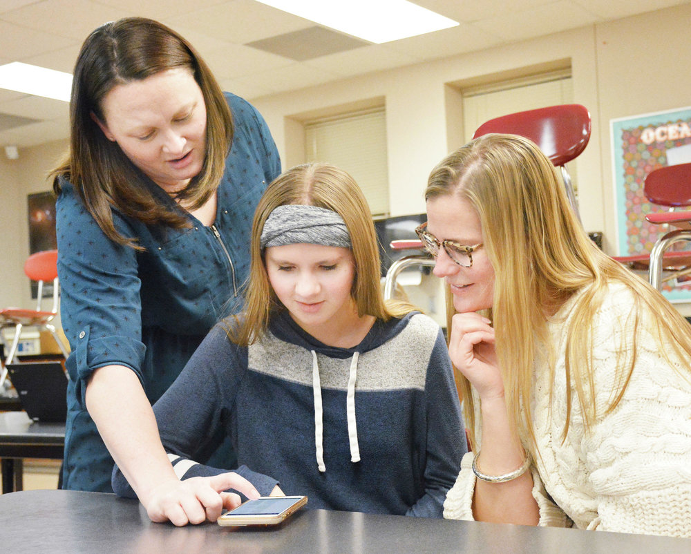 Earth science teacher Rachel Bothun goes over the results of an online schoology quiz taken by Emily Zwach (right), as eighth-grade student Parker Zwach looks on. (Ross Evavold / Echo Press)