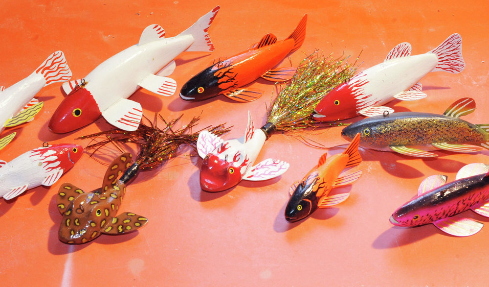 """Working"" decoys carved by Hedlund include brightly-colored fish, as well as frogs with Mylar tails. (Lowell Anderson / Echo Press)"
