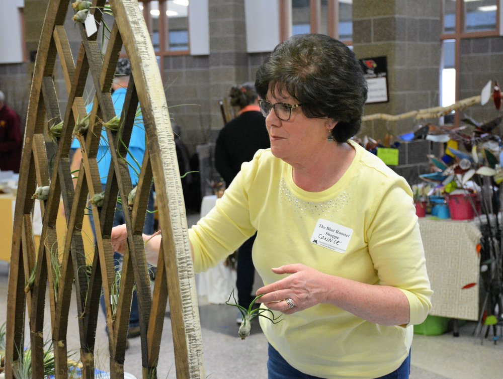 """Connie Simons of the Blue Rooster Shoppe in Alexandria works on decorating a booth at the """"Let's Get Growing"""" workshop at Discovery Middle School Saturday. (Ross Evavold / Echo Press)"""