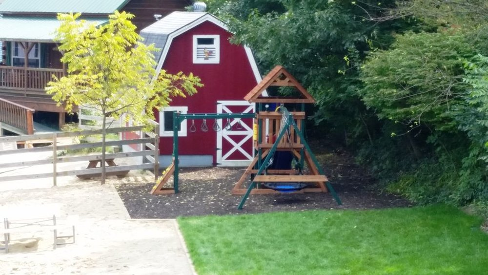 Playscape has 2 lisdes, monkey bars, rock climb wall, swings - in view of deck.