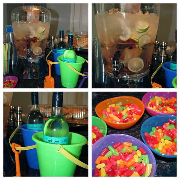 Rainbow water for a colorful birthday party; Wine bottles in a sand bucket @ohbotherblog