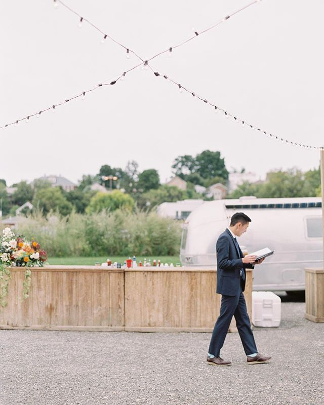 The officiant taking a few pre-ceremony moments to review his notes under our bistro lights at @basilicahudson. . . Photo: @jessicalorren Planning: @nancyharrisevents Florals: @dark_and_diamond . . #lnjwedding #lnjweddings #basilicahudson #basilicahudsonwedding #bistrolights #outdoorcocktailhour #outdoorwedding #bistrolightwedding #weddinglighting #hudsonvalleywedding #upstatewedding #nyweddings